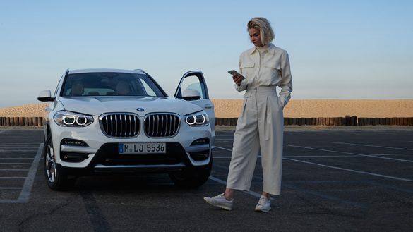 BMW X4 G02 Kataloge App Frau neben BMW 2021